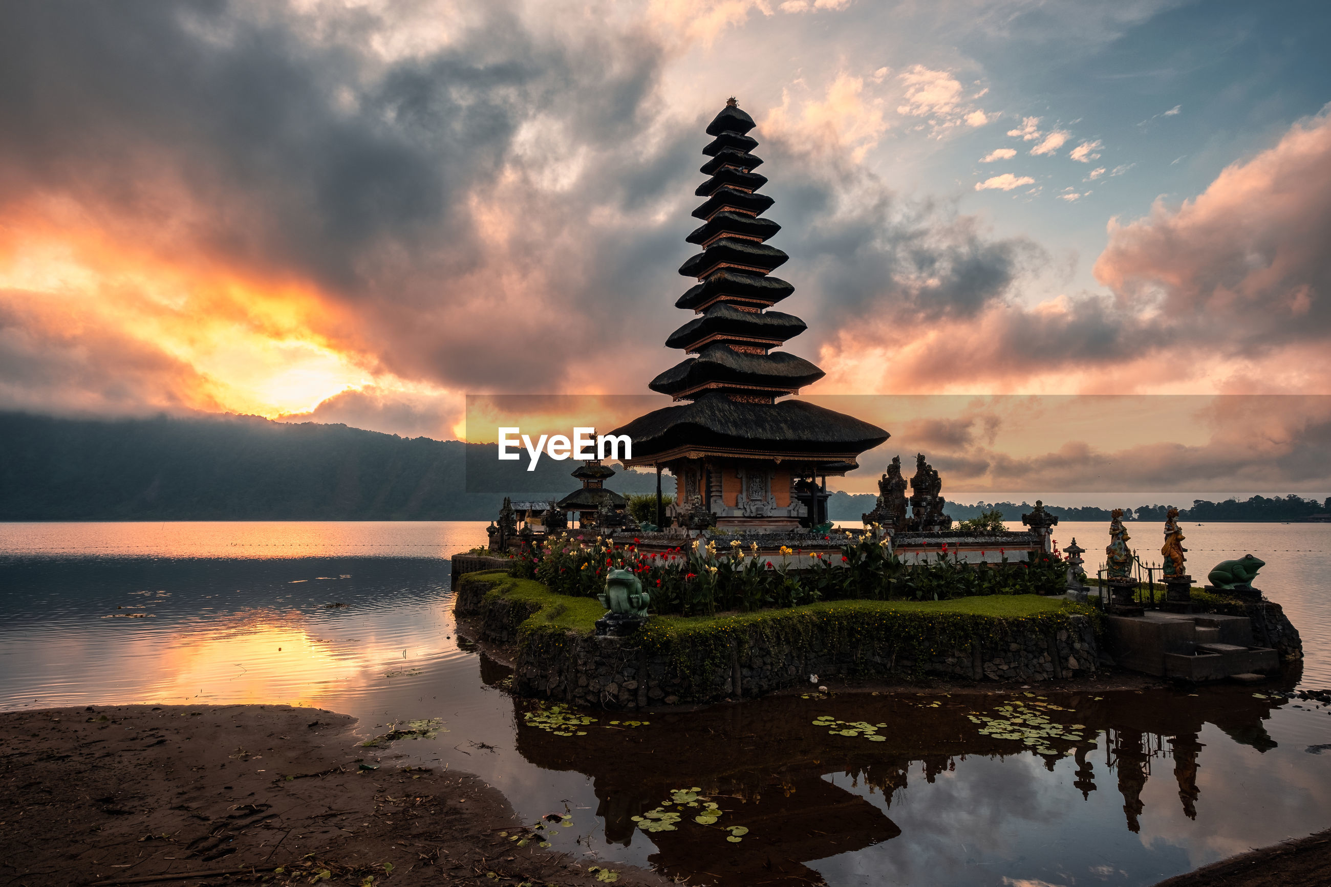 TEMPLE BY LAKE AGAINST SKY DURING SUNSET