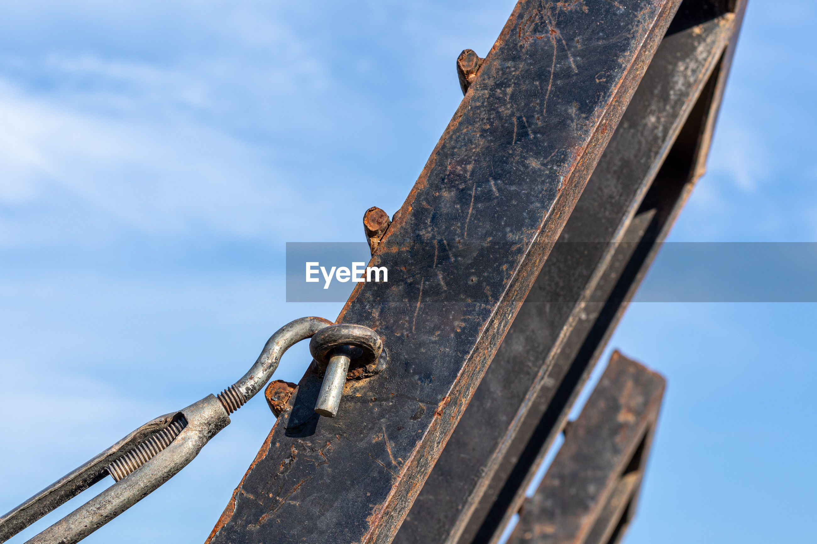 LOW ANGLE VIEW OF OLD RUSTY METALLIC STRUCTURE AGAINST SKY