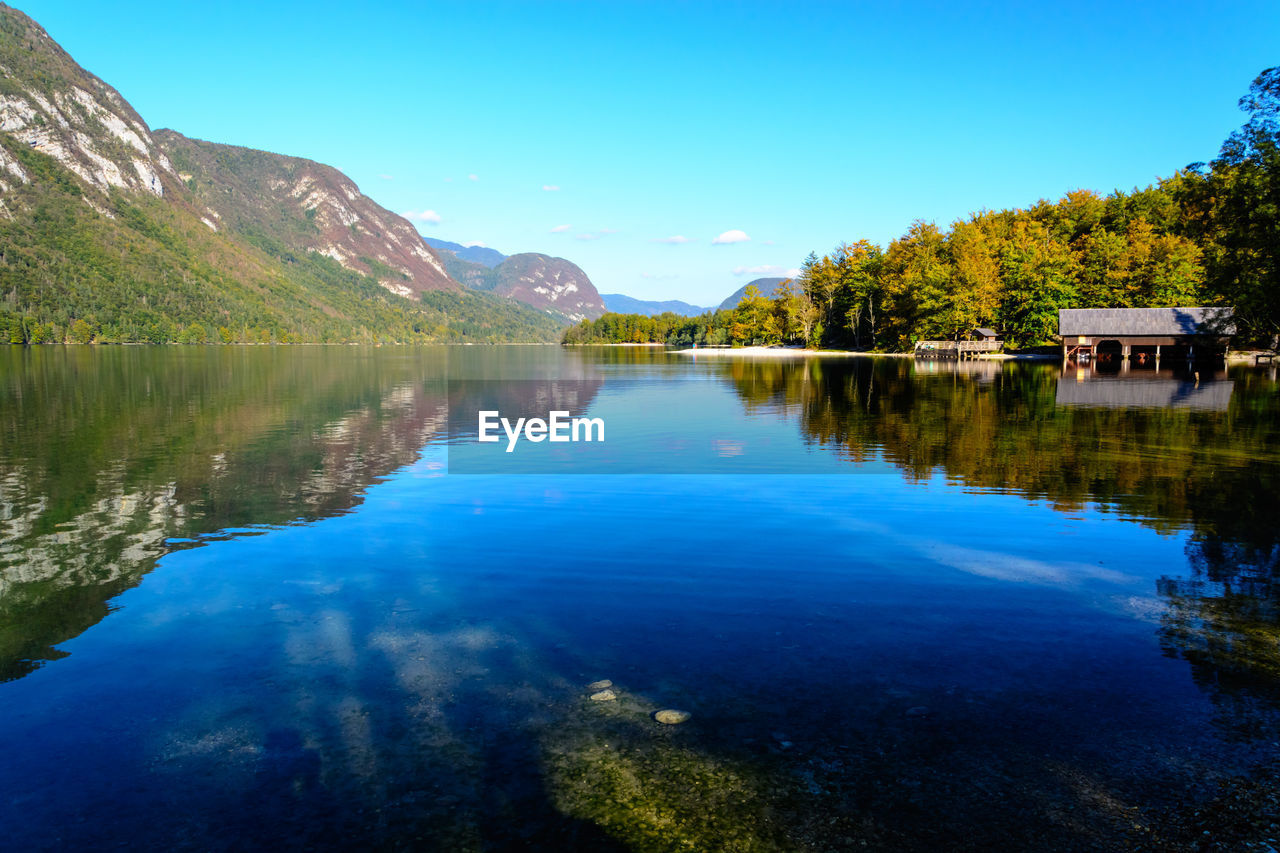 water, reflection, mountain, lake, scenics - nature, beauty in nature, tranquil scene, tranquility, tree, sky, blue, plant, nature, waterfront, no people, day, non-urban scene, idyllic, clear sky, outdoors