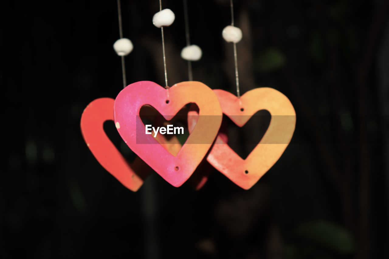 heart shape, love, positive emotion, emotion, no people, close-up, hanging, focus on foreground, text, illuminated, pink color, outdoors, shape, night, design, creativity, decoration, string, western script, black background, valentine's day - holiday