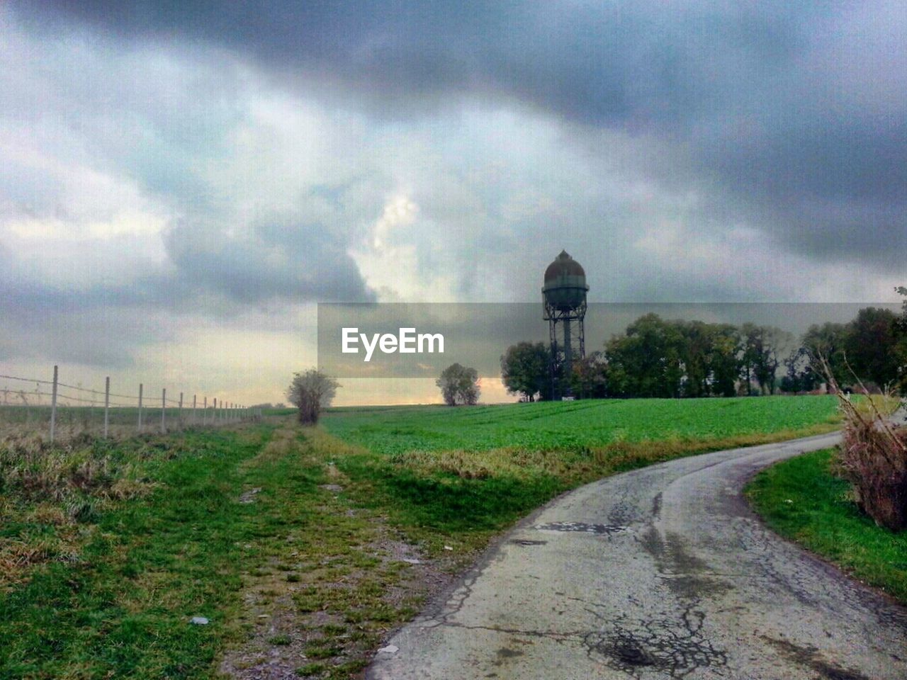 cloud - sky, sky, field, grass, the way forward, tree, day, landscape, nature, no people, outdoors, tranquility, built structure, road, rural scene, water tower - storage tank, scenics, architecture, beauty in nature