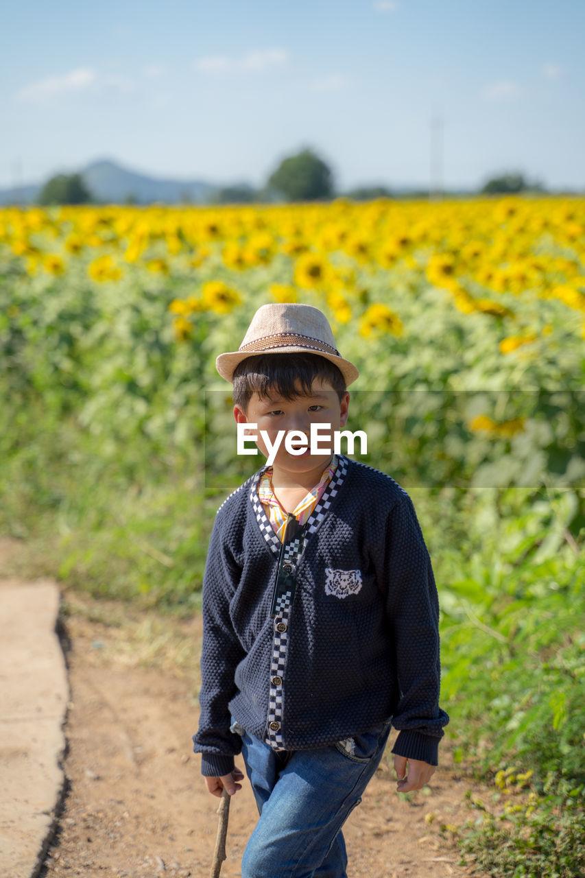Portrait of cute smiling boy in hat standing on field
