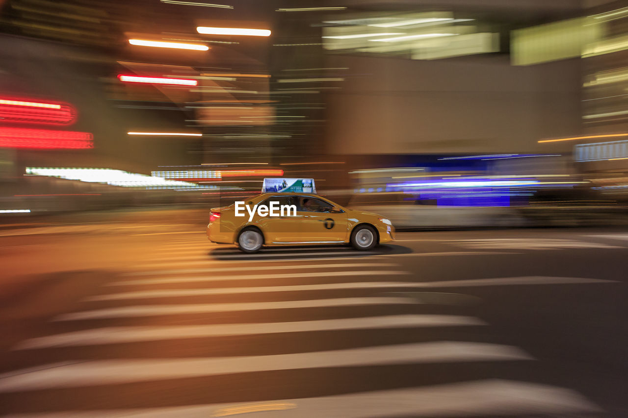 motion, transportation, blurred motion, mode of transportation, car, speed, illuminated, architecture, motor vehicle, land vehicle, night, long exposure, city, on the move, road, street, built structure, building exterior, driving, real people