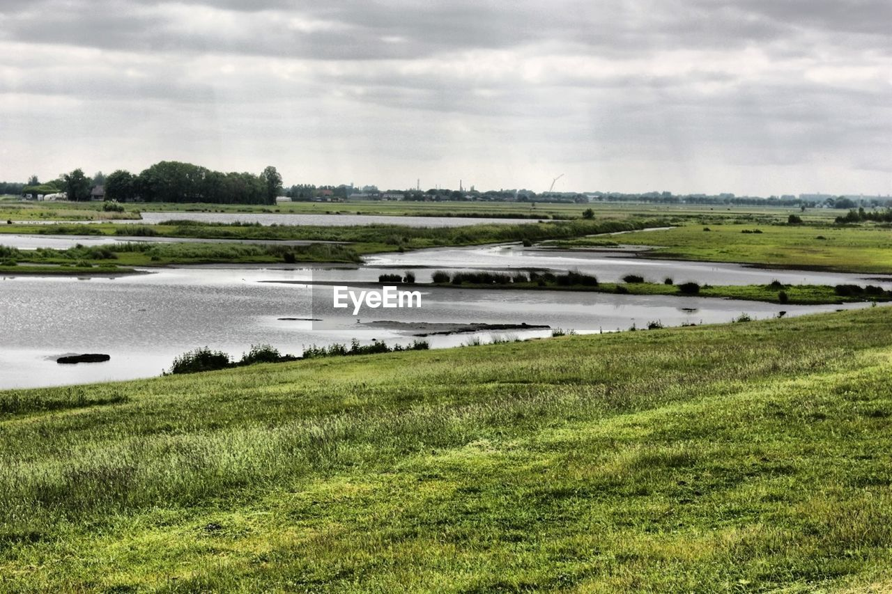 Scenic view of grassy field and lake against cloudy sky