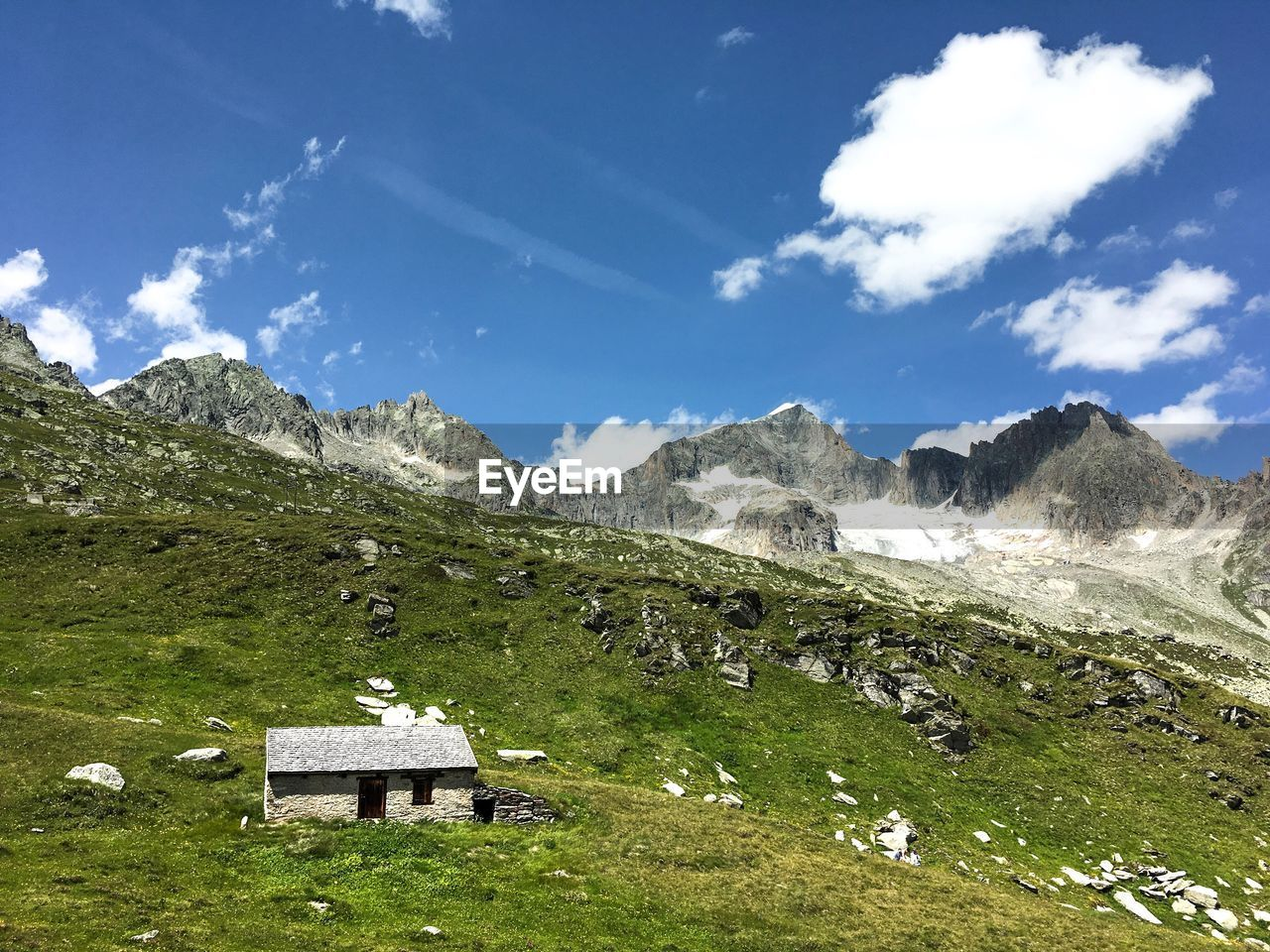 mountain, sky, nature, beauty in nature, scenics, landscape, mountain range, tranquility, tranquil scene, day, cloud - sky, outdoors, grass, built structure, no people, peak, building exterior, architecture, scenery
