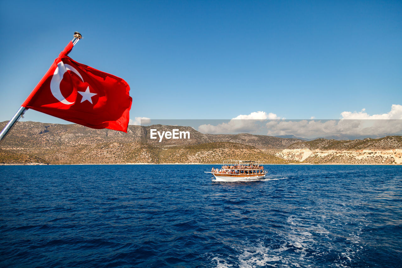 water, nautical vessel, sky, patriotism, waterfront, flag, red, transportation, mode of transportation, nature, sea, beauty in nature, day, scenics - nature, mountain, no people, blue, outdoors, passenger craft