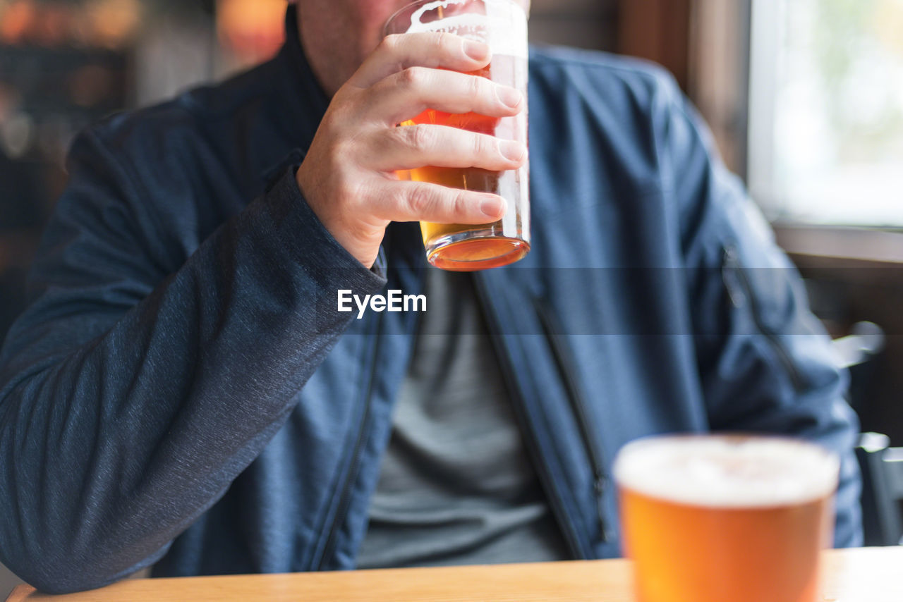 Midsection of man drinking beer in restaurant