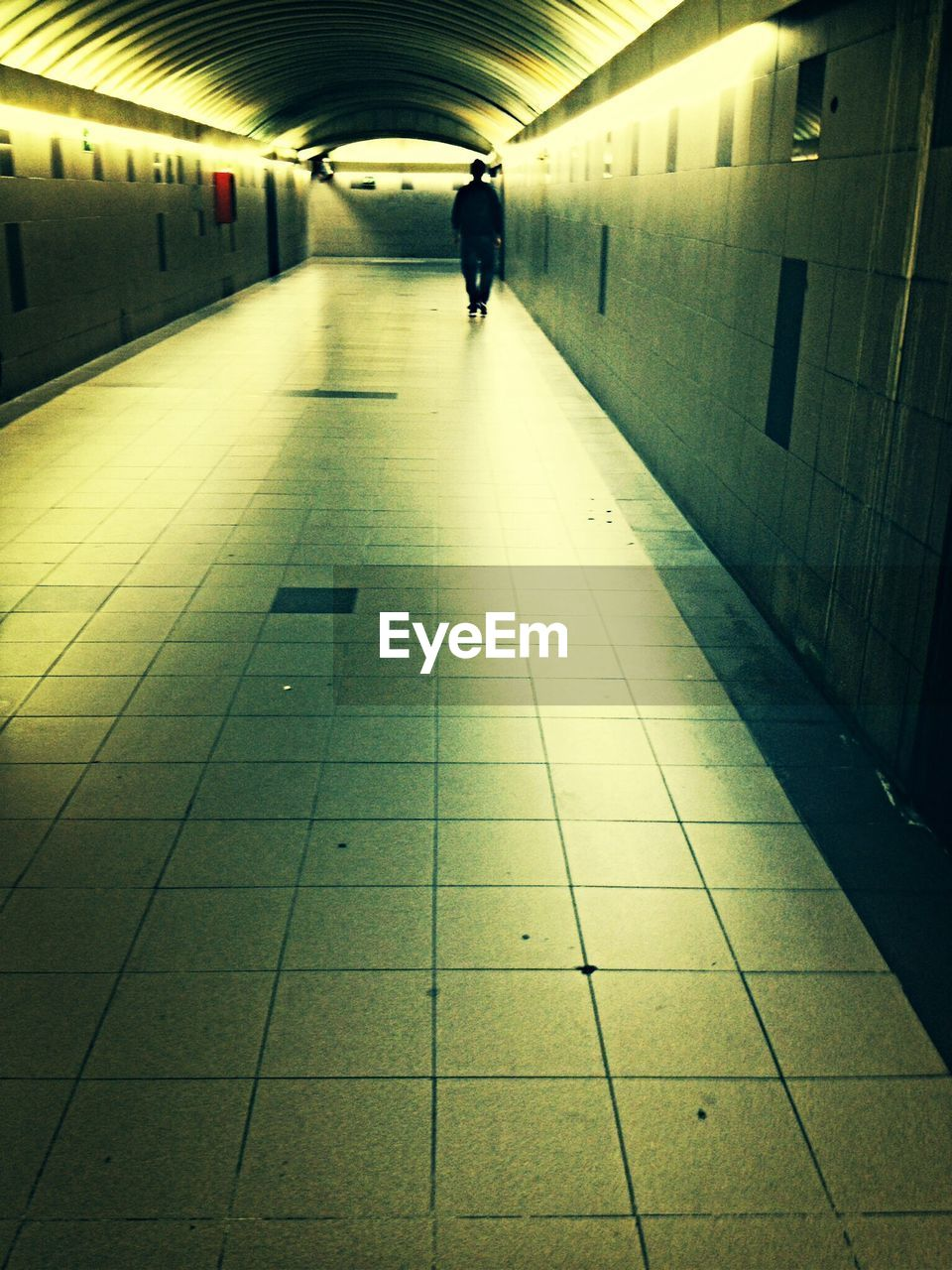 Rear view of person walking in corridor