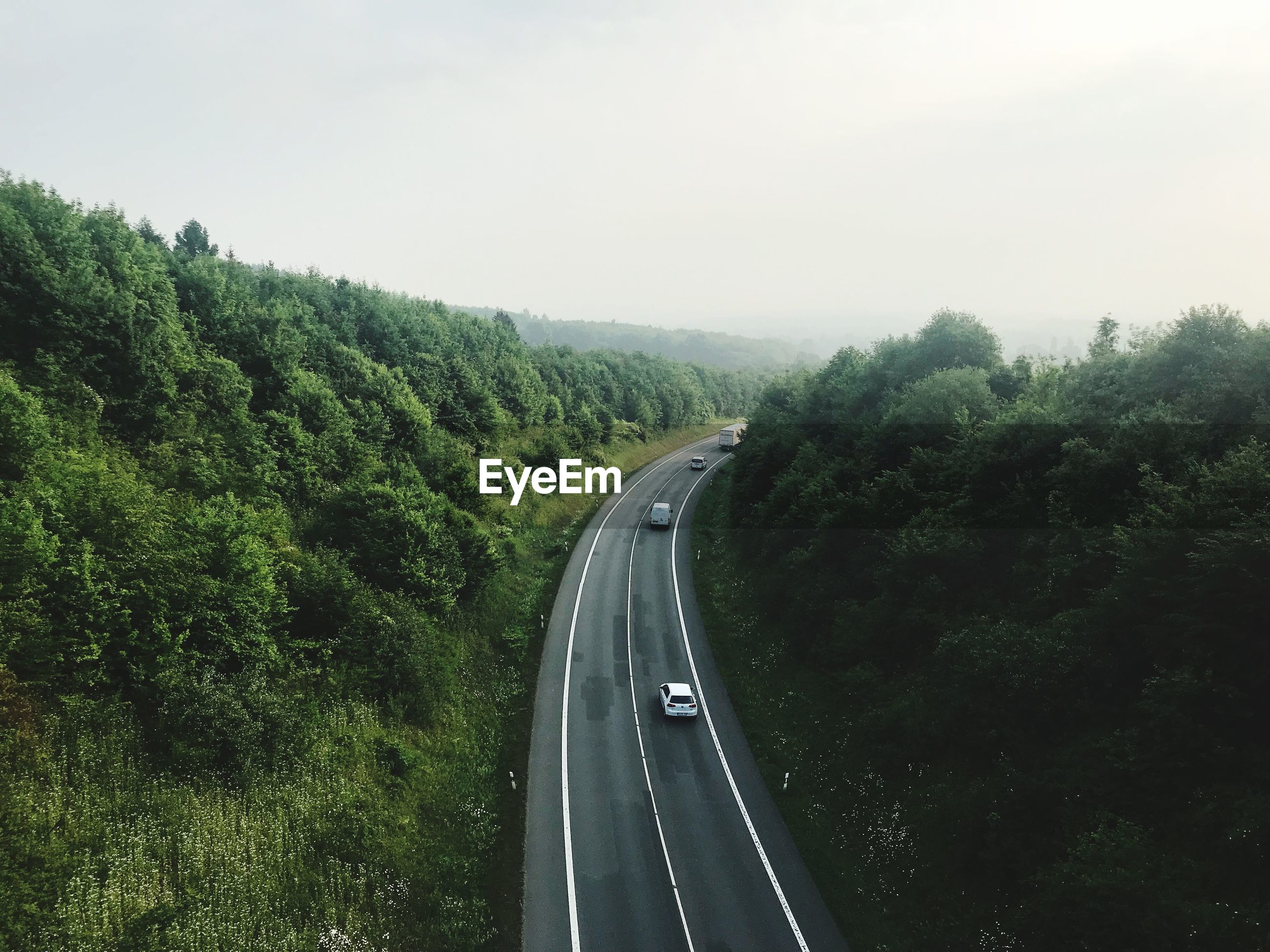 High angle view of cars moving on road amidst trees against sky