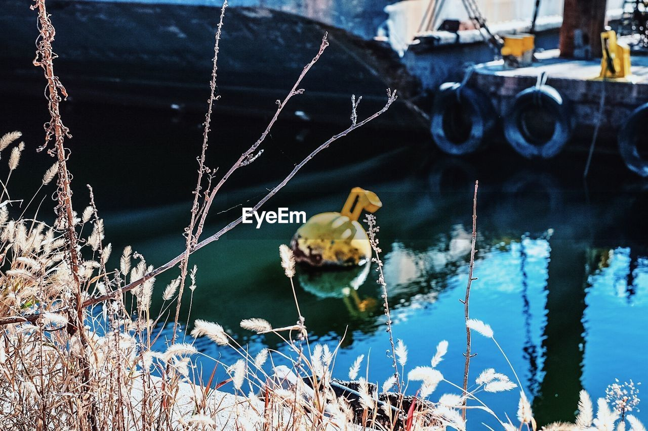 High Angle View Of Buoy Floating By Moored Boat In River