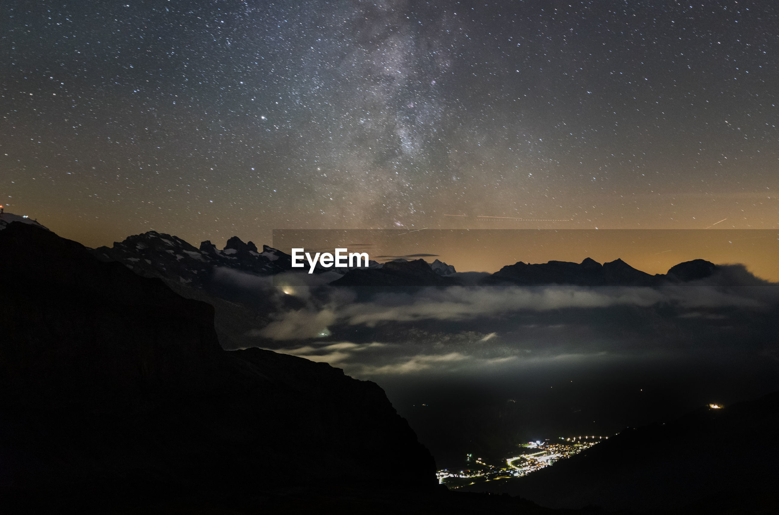 Scenic view of silhouette mountains against sky at night. rugghubel hütte milky way