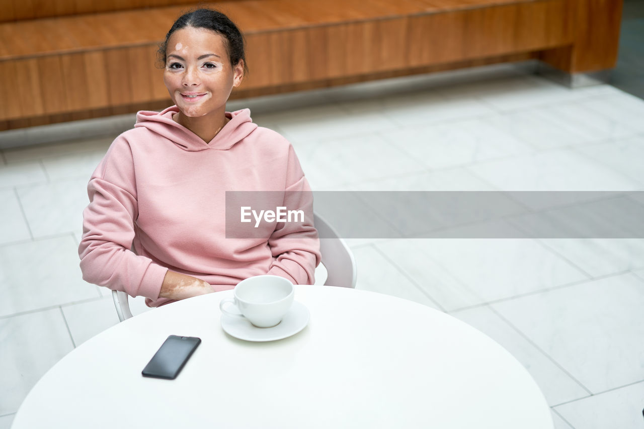 PORTRAIT OF A SMILING YOUNG WOMAN SITTING WITH TABLE