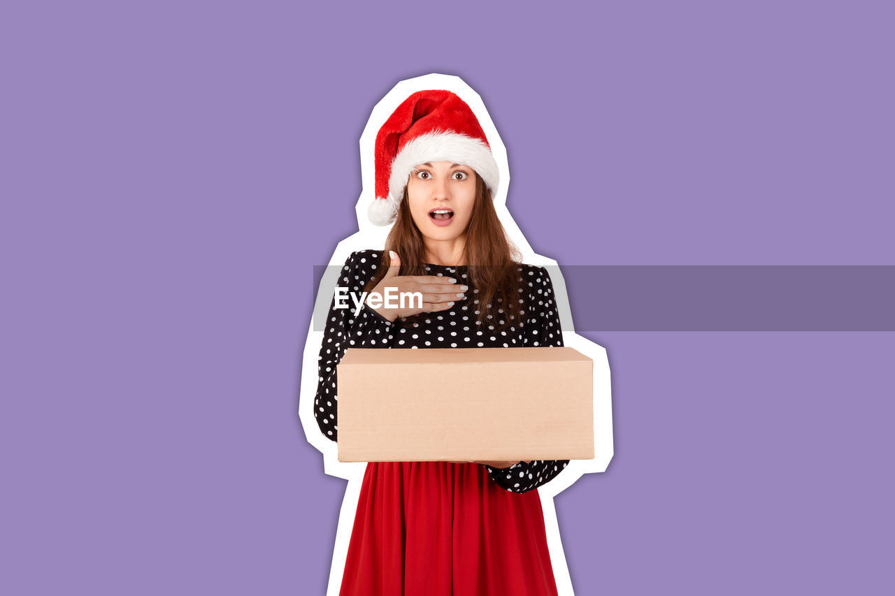 Cut out of young woman holding christmas present against purple background