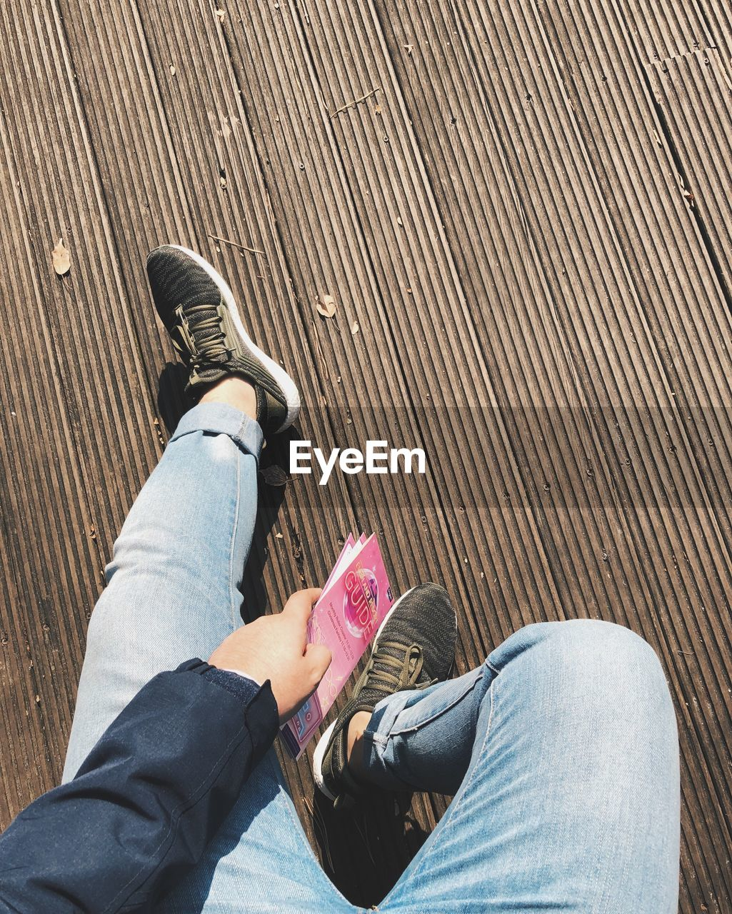 low section, casual clothing, shoe, real people, jeans, human leg, lifestyles, leisure activity, human body part, personal perspective, high angle view, people, body part, day, sitting, men, relaxation, women, adult, outdoors, couple - relationship, wood, human foot