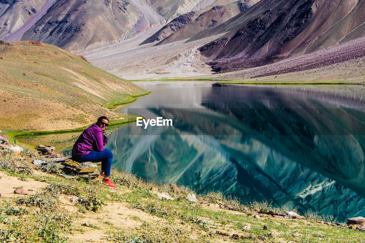 one person, mountain, beauty in nature, scenics - nature, water, environment, adult, adventure, leisure activity, landscape, nature, exploration, activity, real people, hiking, lake, lifestyles, full length, mountain range, looking at view, outdoors