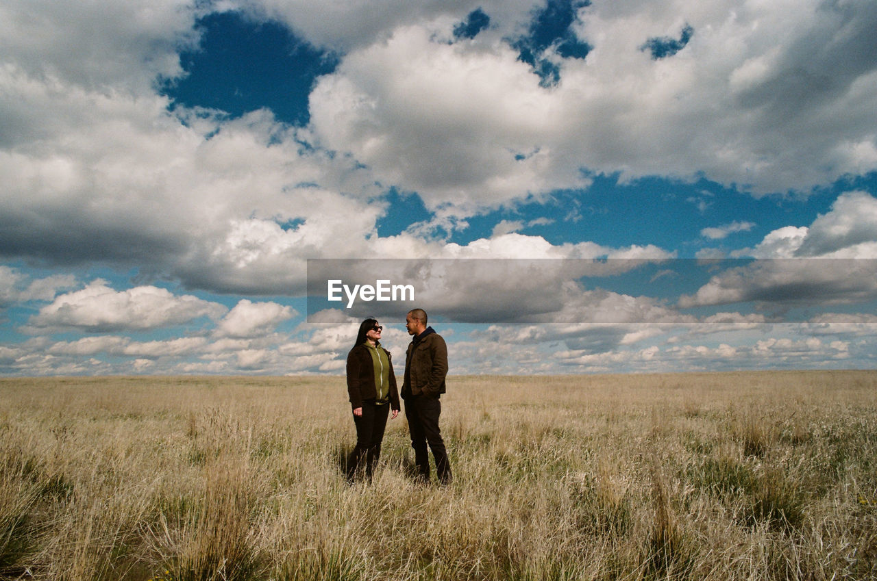 Couple standing on grassy field against cloudy sky