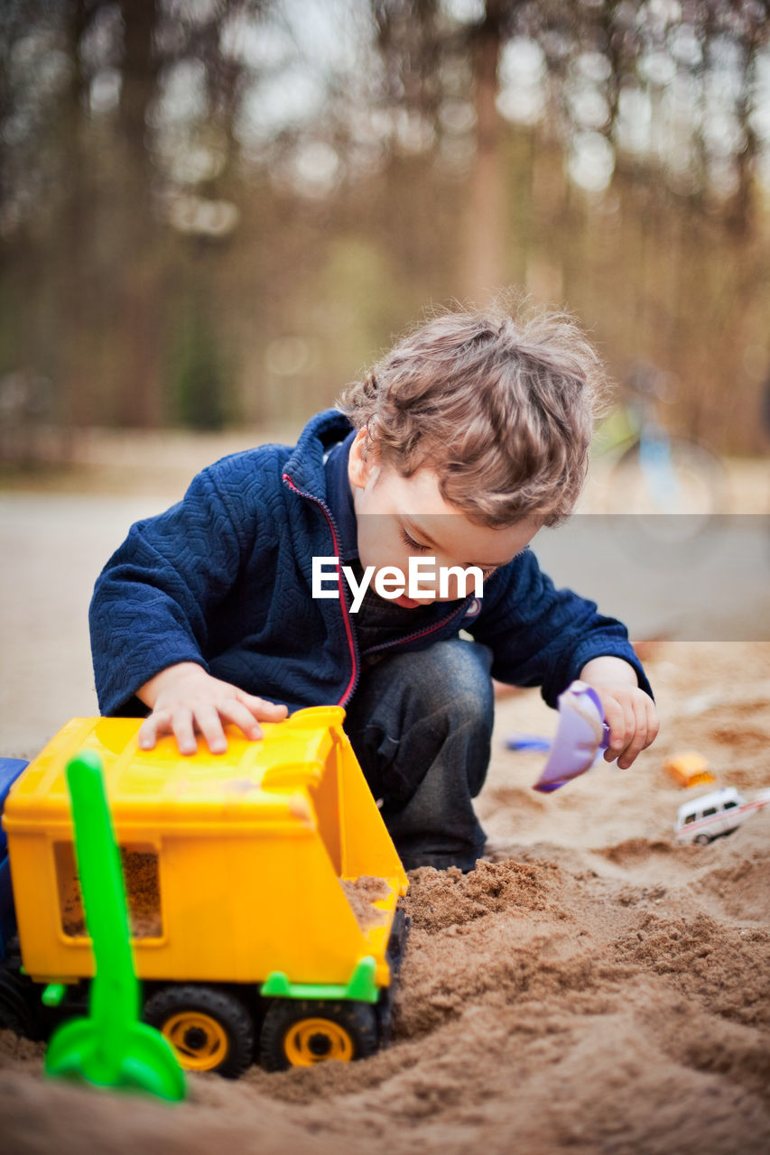 Cute little boy sitting on the sand and playing in a toy car.