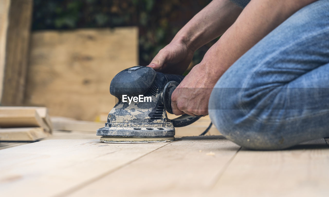 LOW SECTION OF MAN WORKING ON WOOD AGAINST BLURRED BACKGROUND