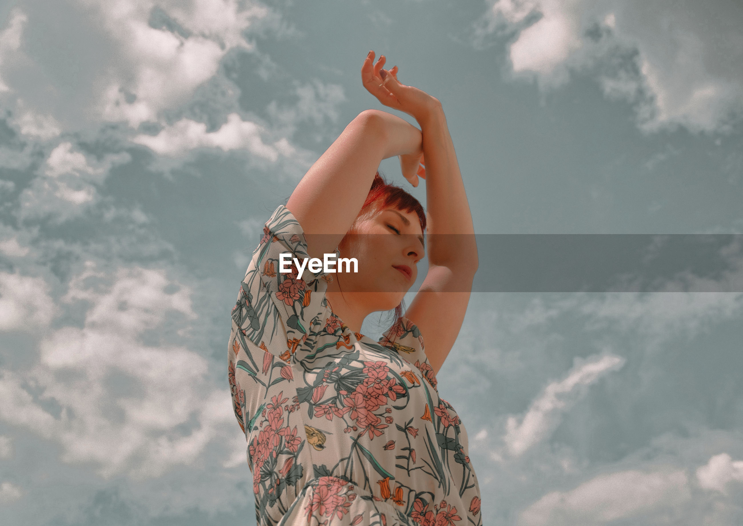 Low angle view of woman with arms raised and closed eyes standing against sky