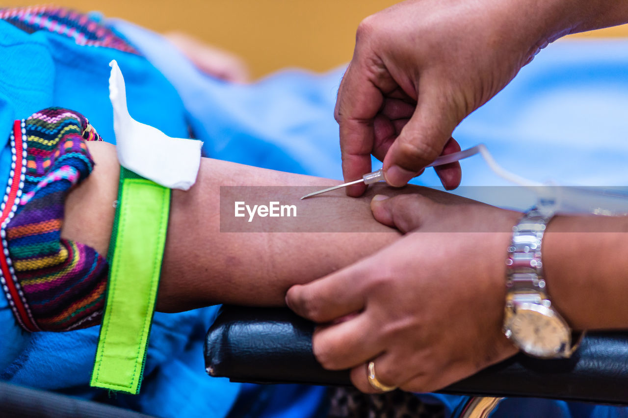 Cropped Hand Of Male Doctor Injecting Needle In Patient Hand On Stretcher