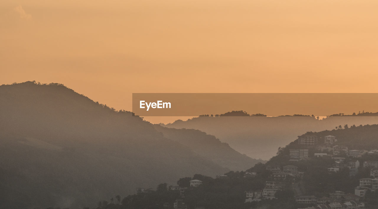 sky, sunset, building exterior, mountain, beauty in nature, architecture, scenics - nature, built structure, no people, nature, orange color, fog, city, tranquil scene, tranquility, mountain range, residential district, cityscape, outdoors, hazy