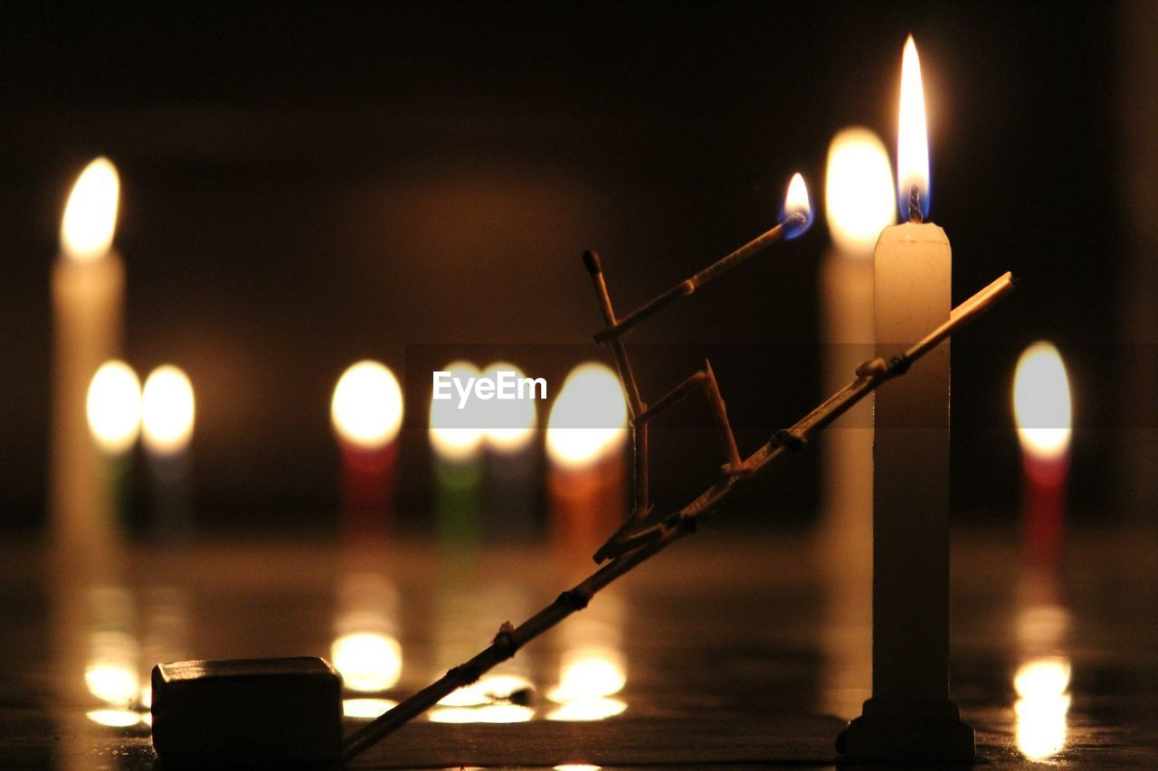 Close-up of creative matchstick male lighting candles at night