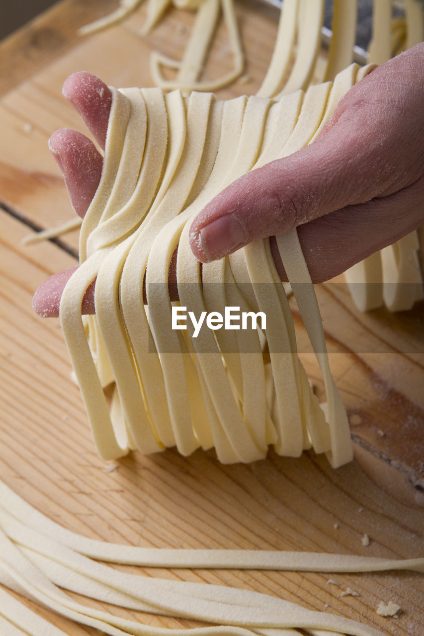 Cropped Hand Holding Raw Pasta On Table