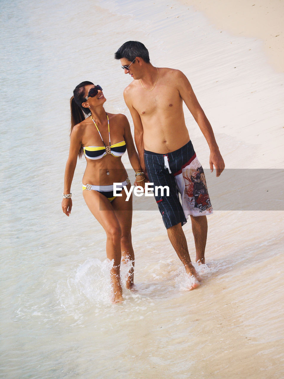 two people, shirtless, togetherness, leisure activity, bikini, sea, young women, young adult, beach, vacations, young men, summer, real people, nature, love, full length, standing, walking, enjoyment, ankle deep in water, water, day, outdoors, lifestyles, men, people