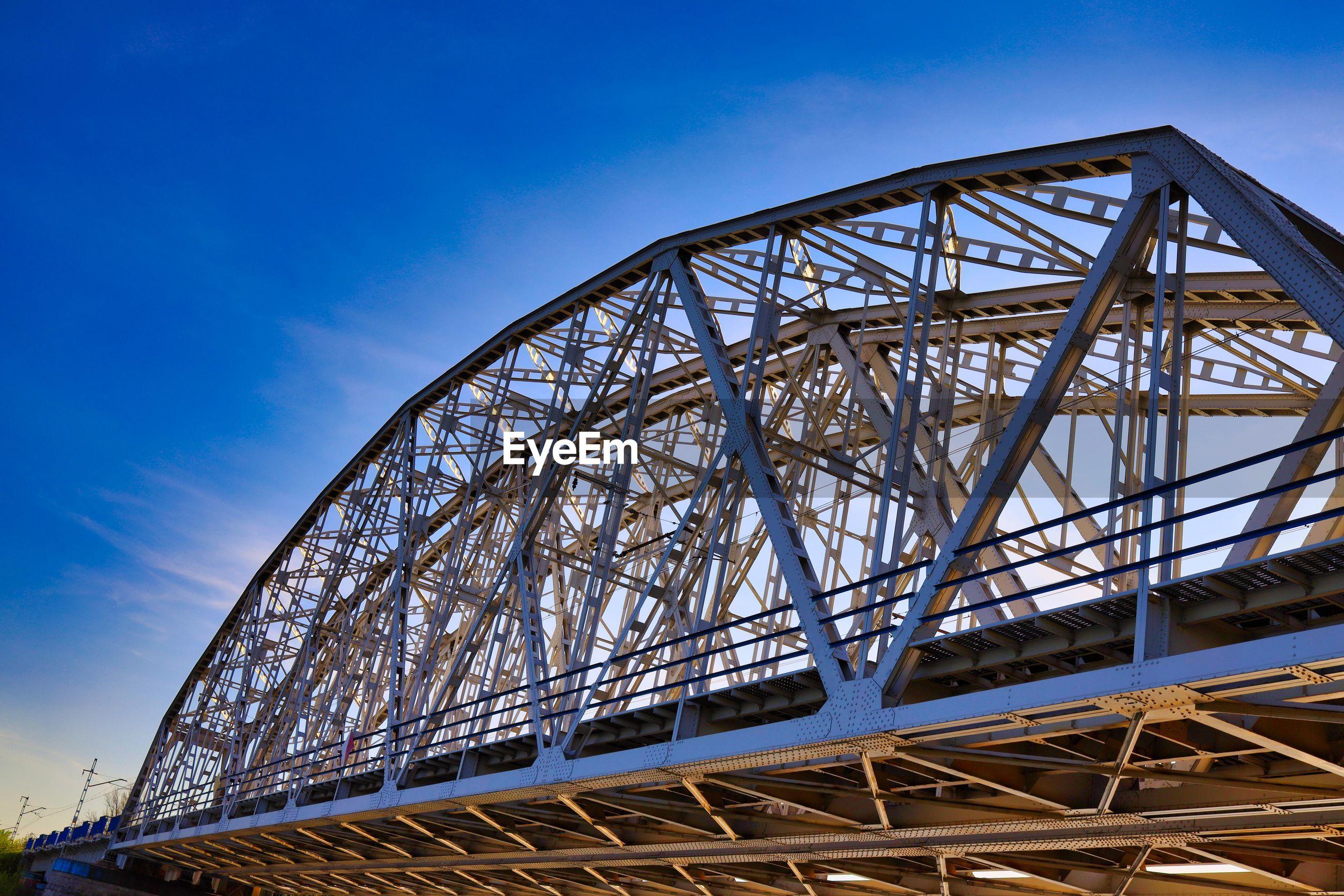LOW ANGLE VIEW OF METALLIC BRIDGE AGAINST BLUE SKY