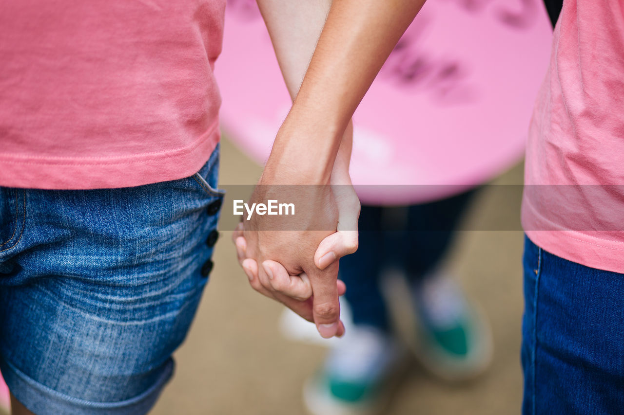 Midsection Of Man And Woman Holding Hands Outdoors
