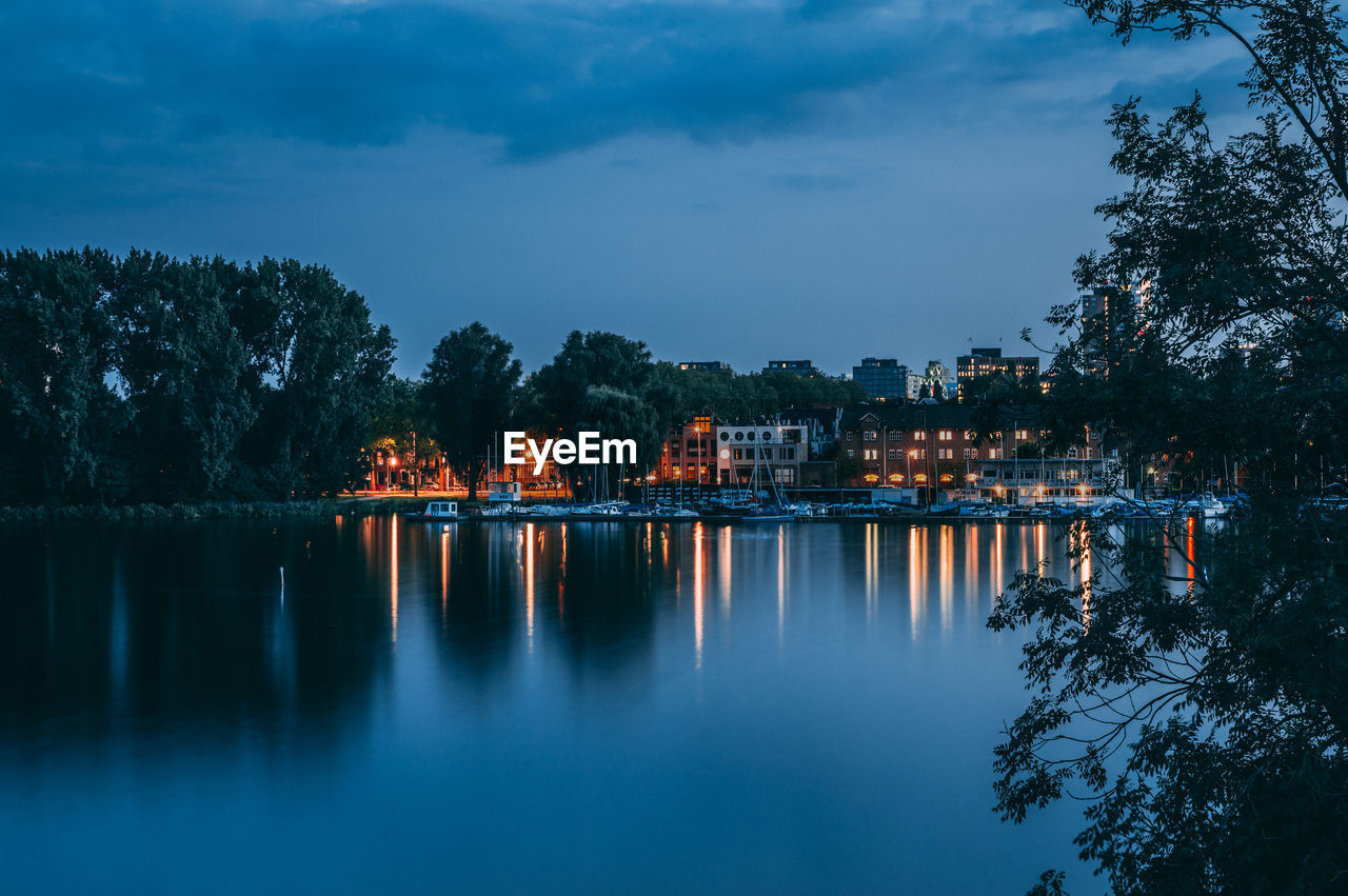 Illuminated City By Lake Against Sky At Dusk
