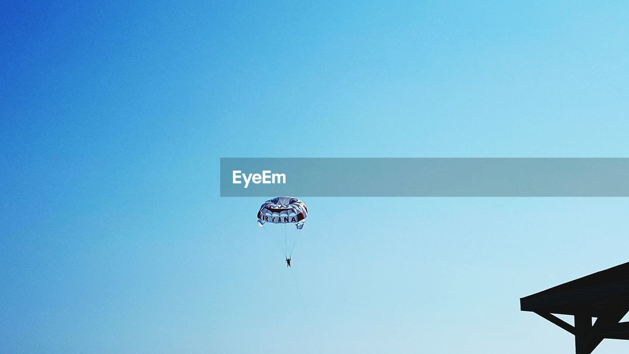 parachute, adventure, clear sky, leisure activity, low angle view, copy space, extreme sports, real people, outdoors, blue, day, skydiving, sport, paragliding, nature, one person, sky, people