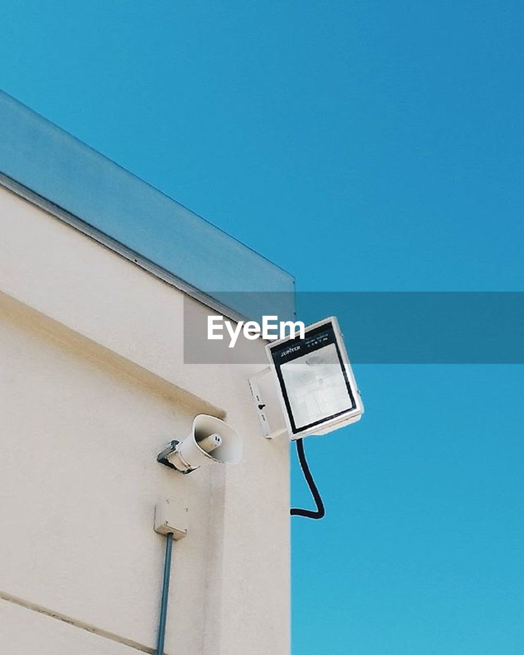 low angle view, security camera, blue, clear sky, no people, building exterior, built structure, outdoors, day, architecture, sky