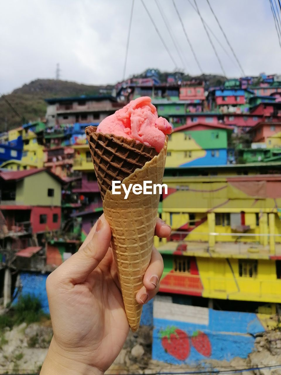 human hand, ice cream, hand, frozen food, sweet food, sweet, dairy product, frozen, human body part, indulgence, holding, one person, real people, ice cream cone, food, cone, food and drink, dessert, focus on foreground, personal perspective, temptation, body part, outdoors, finger