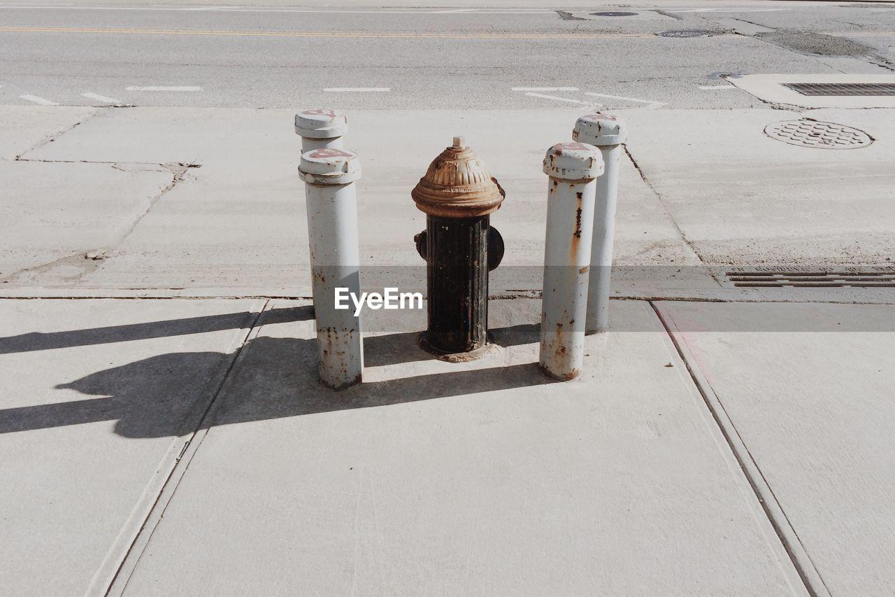 High Angle View Of Fire Hydrant Amidst Rusty Metallic Bollards On Sidewalk