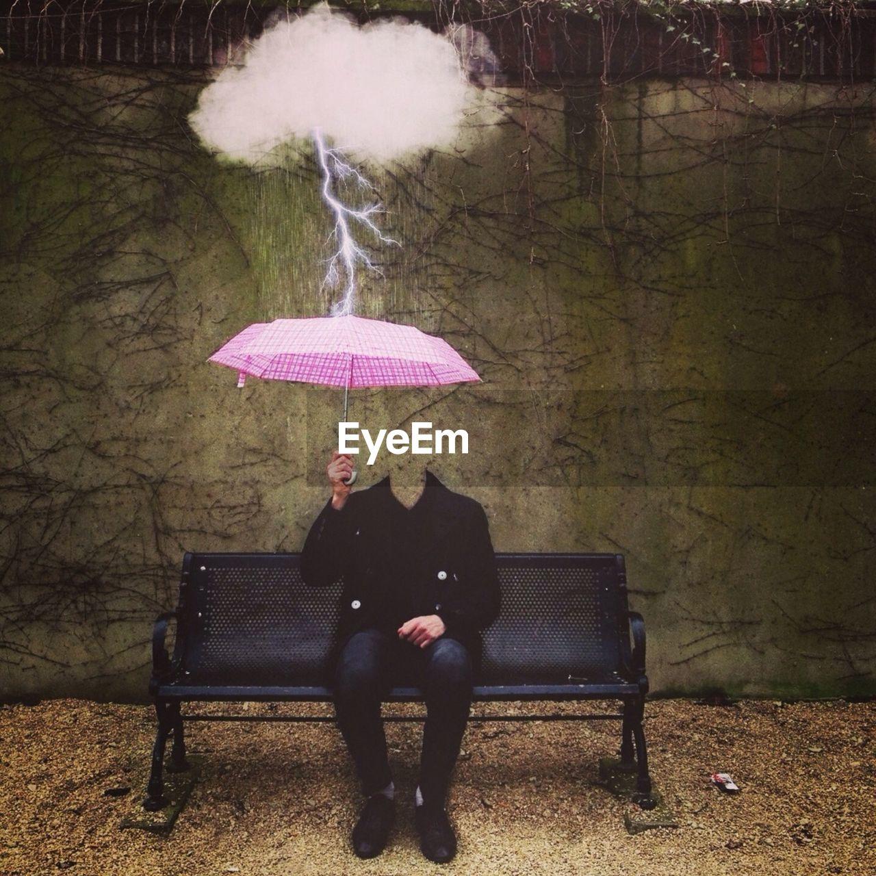 Decapitated man sitting under pink umbrella