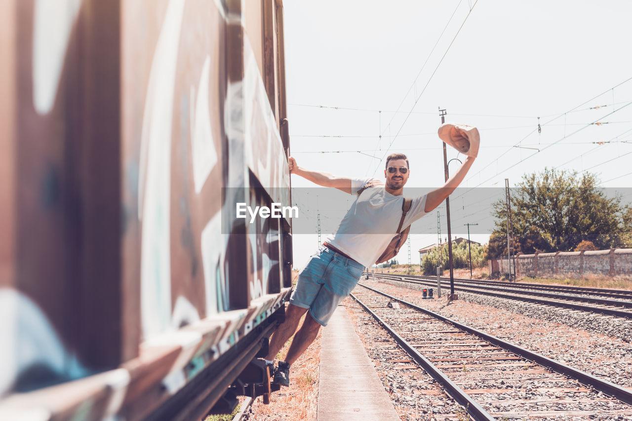 Full length of man hanging on train against sky