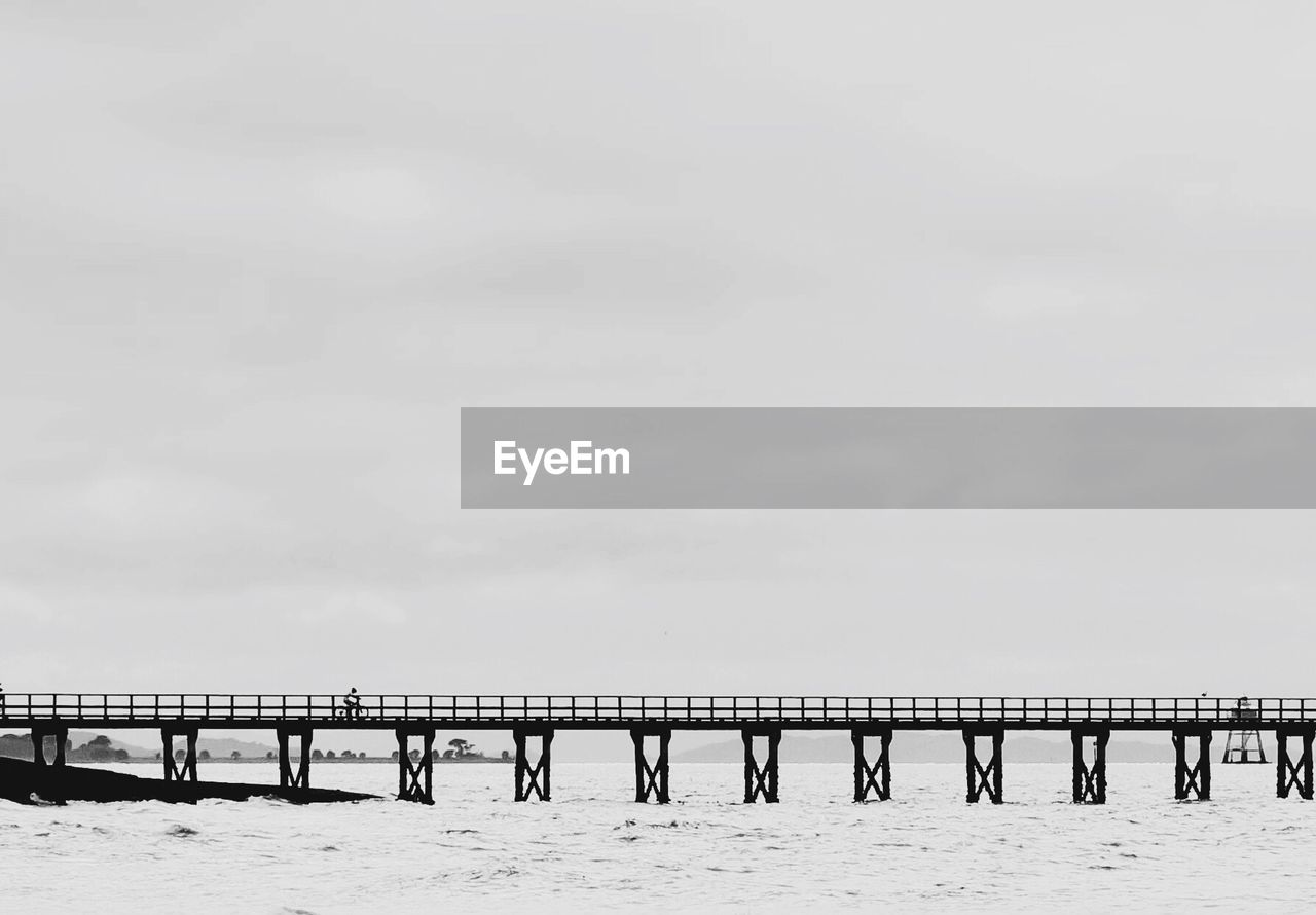 Side View Of Bridge Over Calm Sea Against Sky