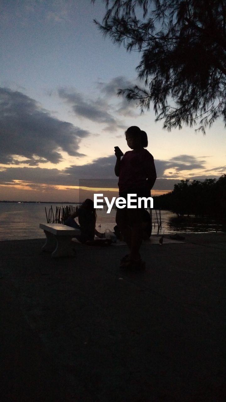sunset, real people, silhouette, sky, sea, nature, rear view, beach, scenics, leisure activity, full length, men, beauty in nature, water, outdoors, lifestyles, cloud - sky, tranquil scene, standing, nautical vessel, tree, horizon over water, day, people