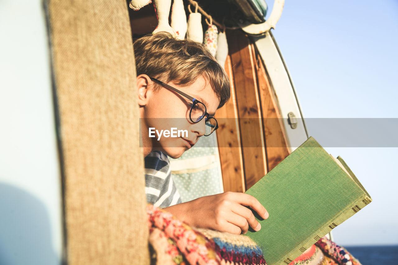 Boy reading book while lying in camper van