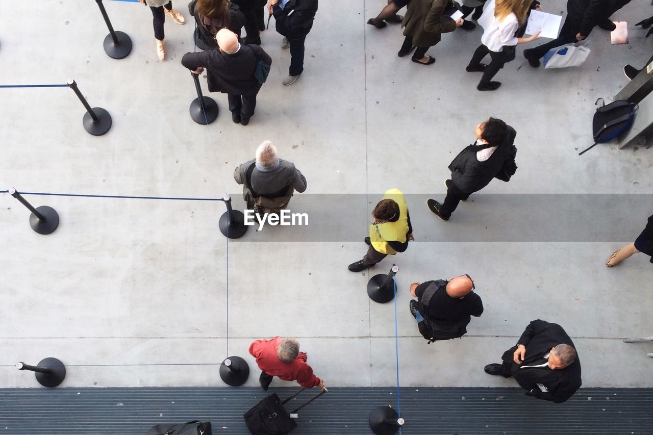 High Angle View Of People Standing By Stanchion On Floor