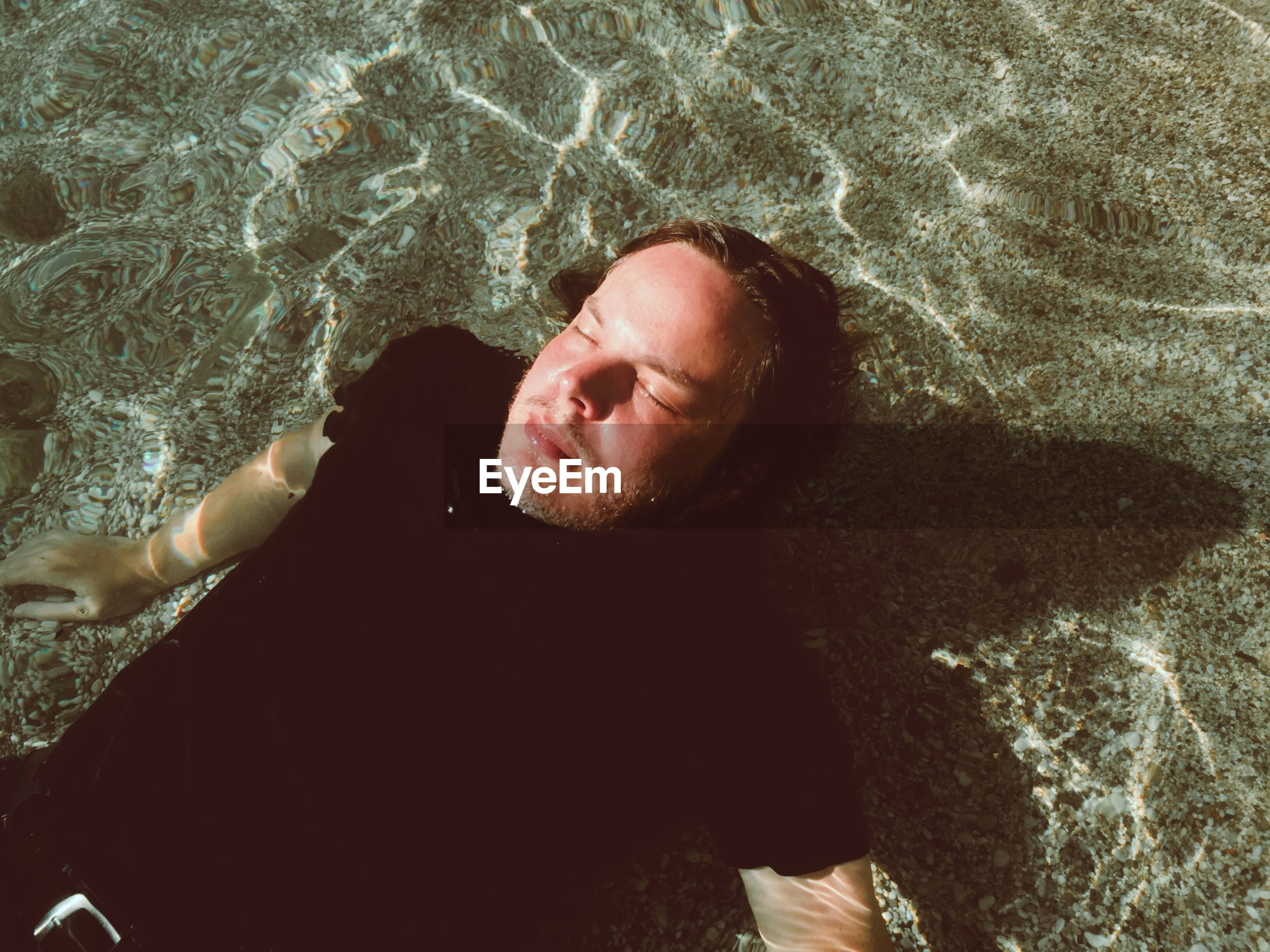 High angle view of man lying in water at beach