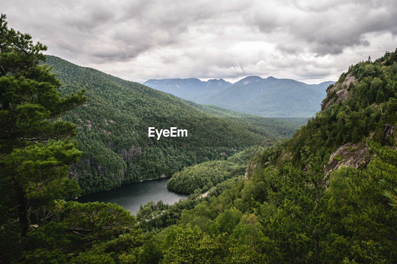 SCENIC VIEW OF RIVER AMIDST GREEN MOUNTAINS AGAINST SKY
