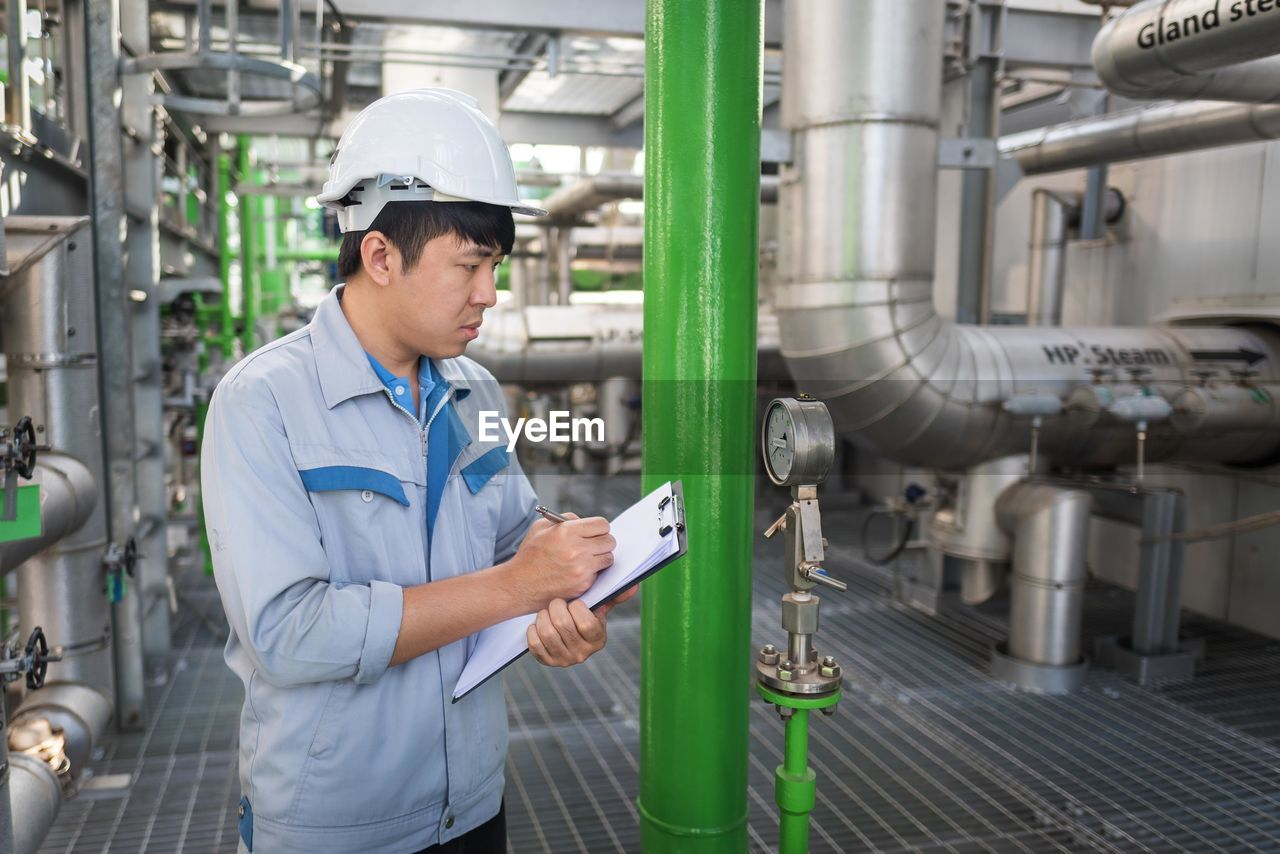 Worker holding clipboard while working in factory