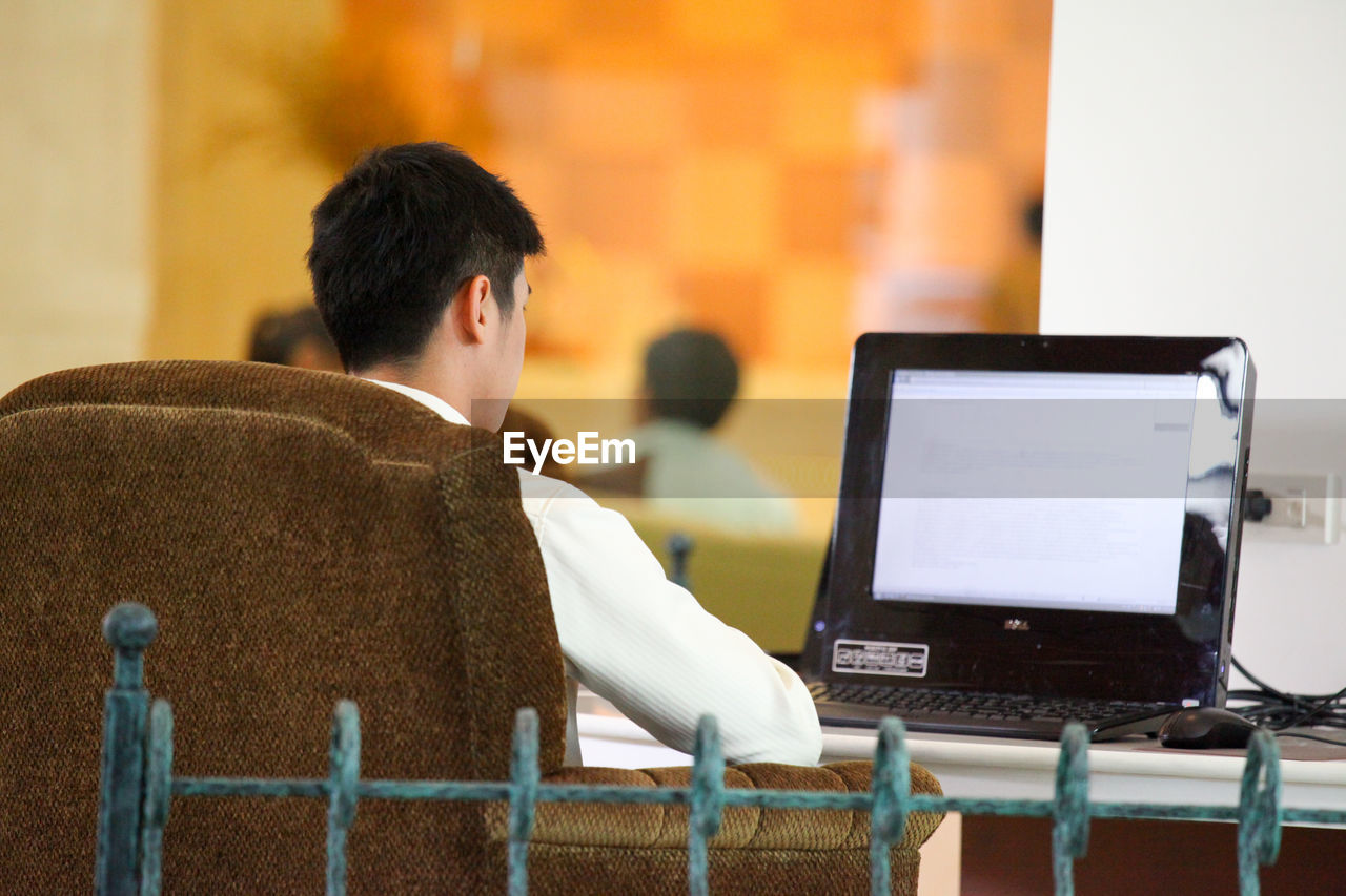 technology, wireless technology, communication, computer, real people, focus on foreground, sitting, laptop, rear view, one person, men, table, connection, using laptop, indoors, portable information device, adult, young men, lifestyles