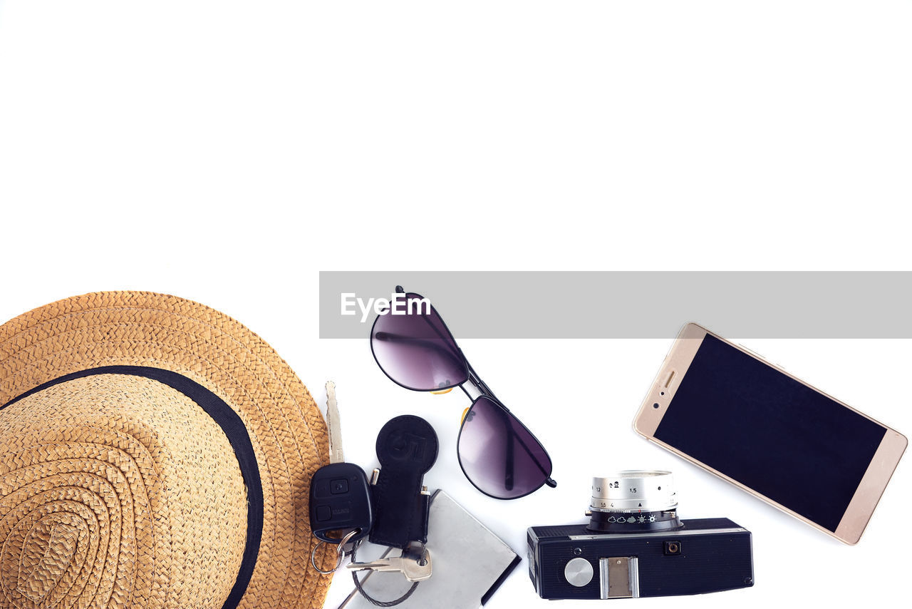 technology, studio shot, white background, indoors, copy space, communication, hat, no people, still life, connection, glasses, fashion, wireless technology, close-up, smart phone, sunglasses, portable information device, screen, headphones, personal accessory, digital camera