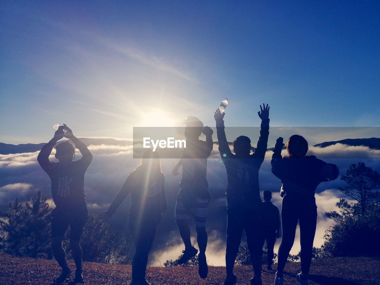 sky, group of people, real people, leisure activity, arms raised, human arm, togetherness, lifestyles, friendship, sunlight, men, land, women, lens flare, nature, standing, emotion, enjoyment, positive emotion, sun, limb, outdoors, excitement, bright
