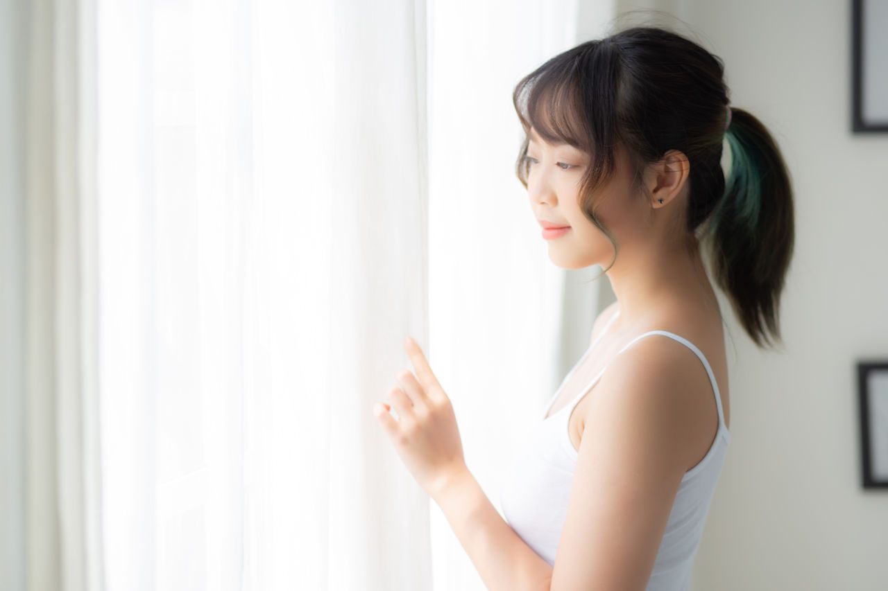 one person, indoors, lifestyles, young women, real people, young adult, women, standing, curtain, beauty, looking, adult, beautiful woman, window, white color, leisure activity, contemplation, casual clothing, tank top, hairstyle