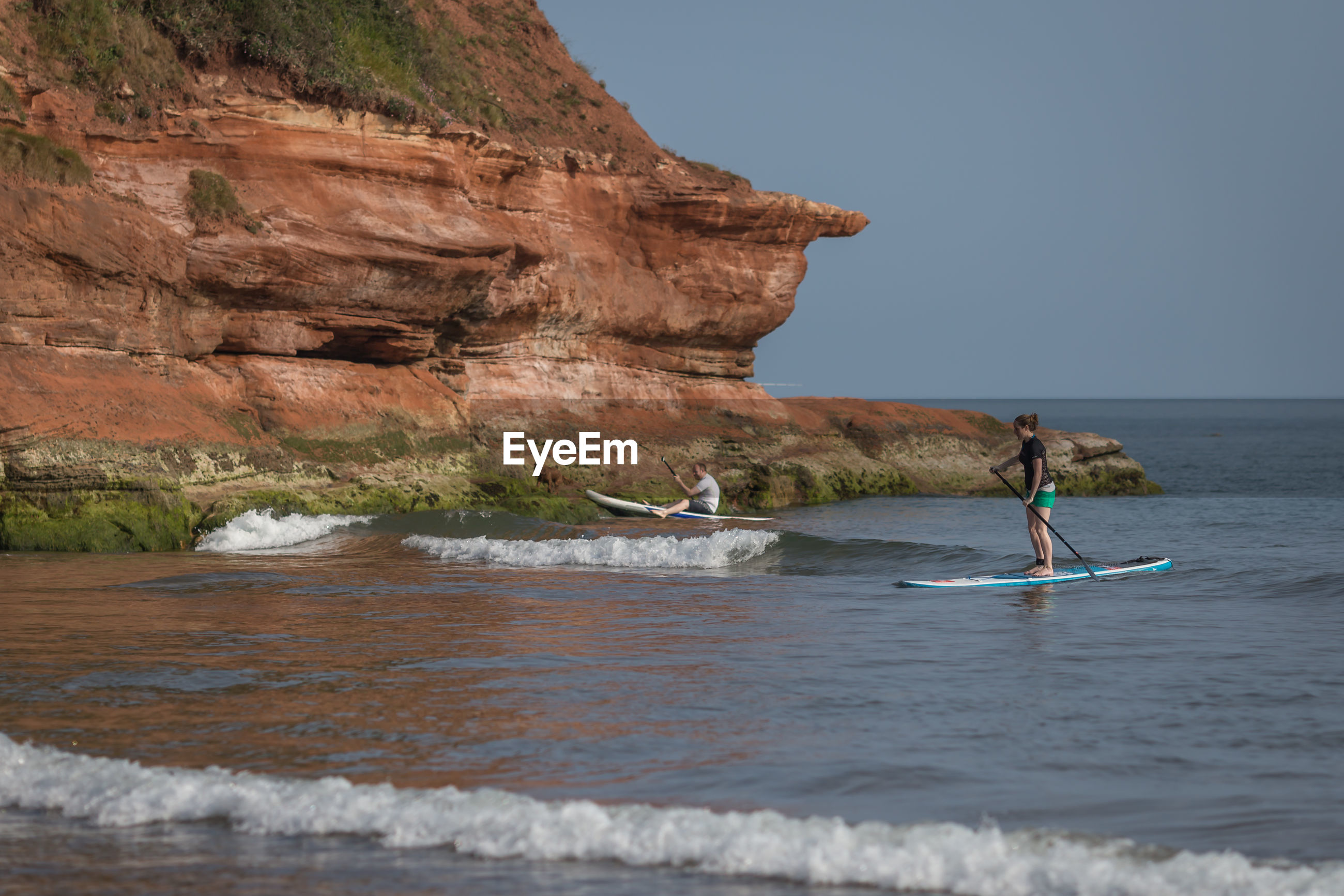 Man and woman paddleboarding in sea against rocky cliff