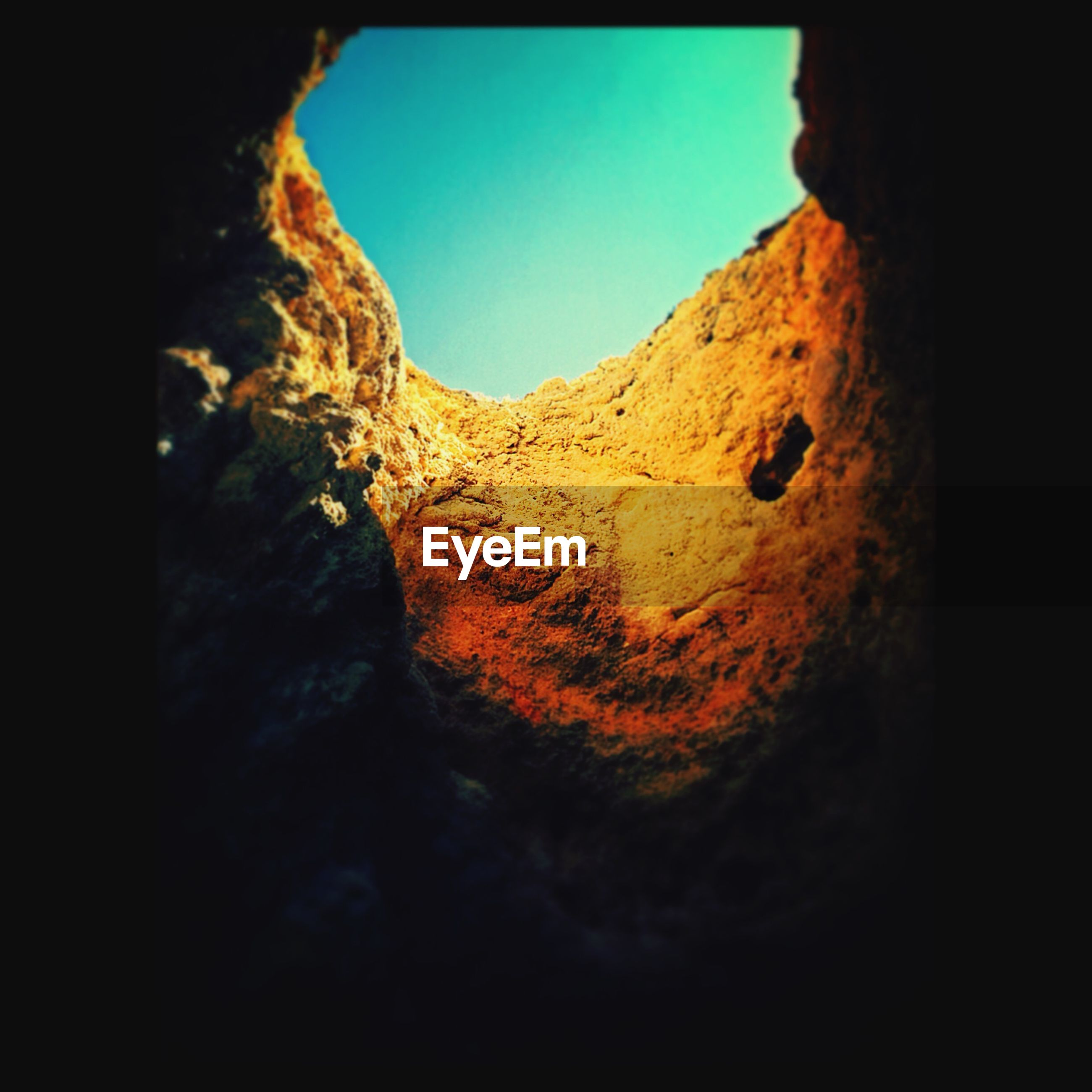 Low angle view of clear sky seen from cave